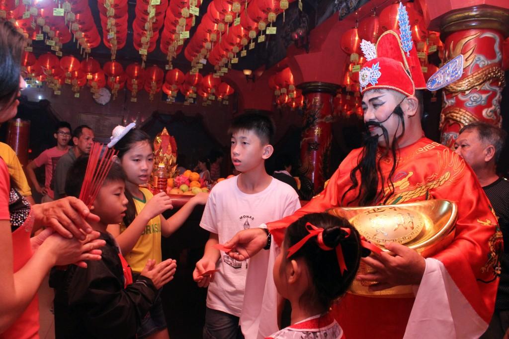 Pengurus Vihara dengan berdandan ala Dewa Uang Cai Shen membagikan angpao dan coklat kepada warga yang mengikuti sembahyangan imlek di Vihara Nimala, Tangerang, Banten, Rabu (18/2)malam. Pembagian angpao merupakan tradisi yang sering dilakukan pada perayaan Imlek yang mengambil kisah cerita dari Dewa Uang China Cei Shen. ANTARA FOTO/Muhammad Iqbal/ss/pd/15