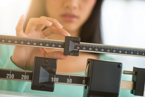 midsection-of-woman-adjusting-weight-scale-768x513